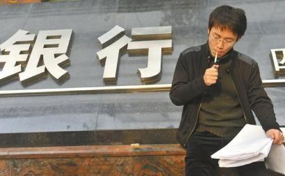 11月18日,在银行门口的陈先生无助地抽着烟。